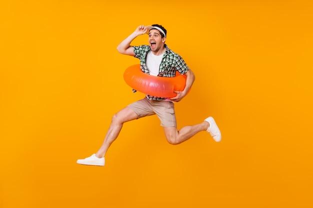 Emotionele man in hoge geesten springt op oranje ruimte met opblaasbare cirkel en neemt zijn pet af.