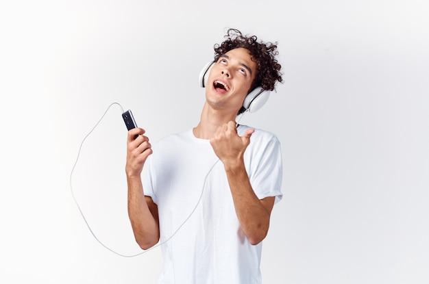 Emotionele man in wit t-shirt luisteren naar muziek met koptelefoon