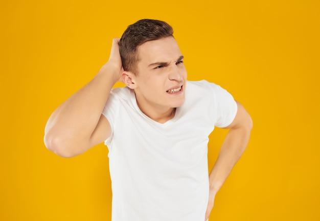 Emotionele man in witte t-shirt gebaren met zijn handen studio