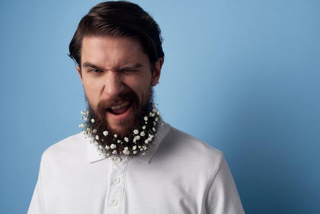 Emotionele man met bloemen in een baard wit overhemd blauwe achtergrond