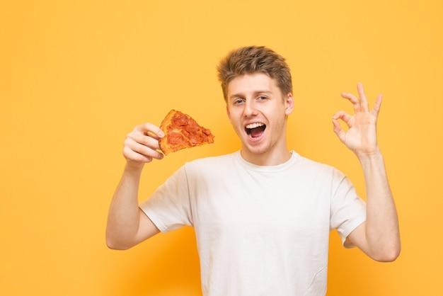 Emotionele man met een stuk pizza in zijn handen toont een gebaar van ok
