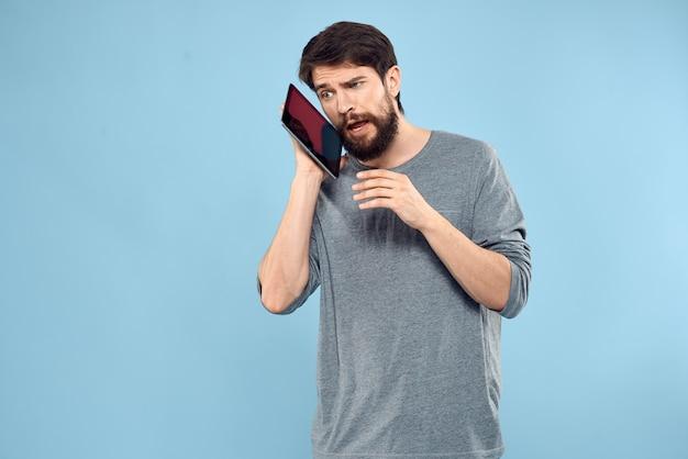 Emotionele man met een tablet in de handen van een draadloos apparaat
