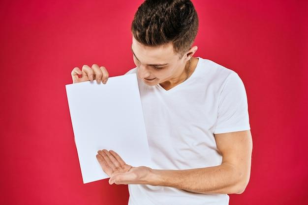 Emotionele man met een vel papier kopie ruimte t-shirt rode achtergrond
