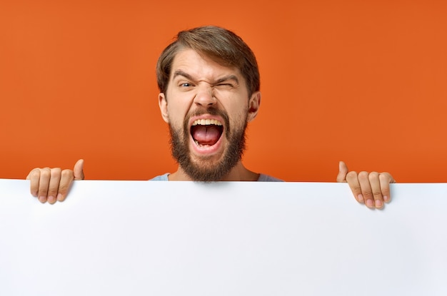 Emotionele man met een wit vel papier in zijn handen poster mockup reclamebord. hoge kwaliteit foto