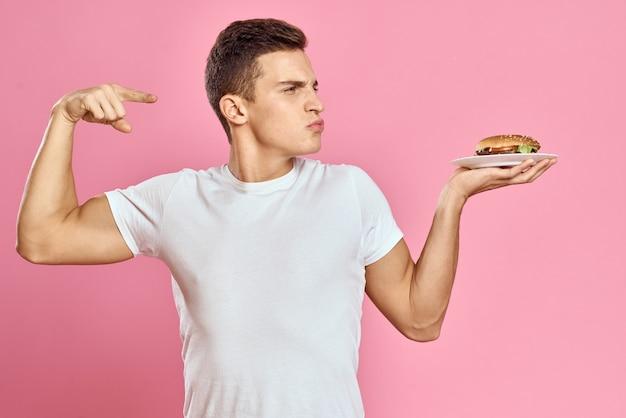 Emotionele man met hamburger op een bord en wit t-shirt roze achtergrond weergave van fastfood calorieën bijgesneden. hoge kwaliteit foto