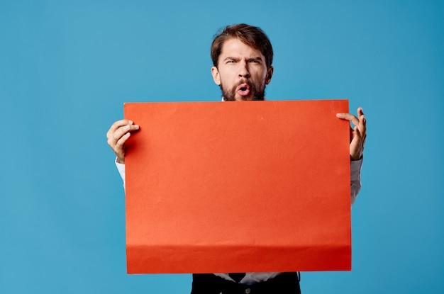 Emotionele man met rode banner communicatie reclame geïsoleerde blauwe muur.