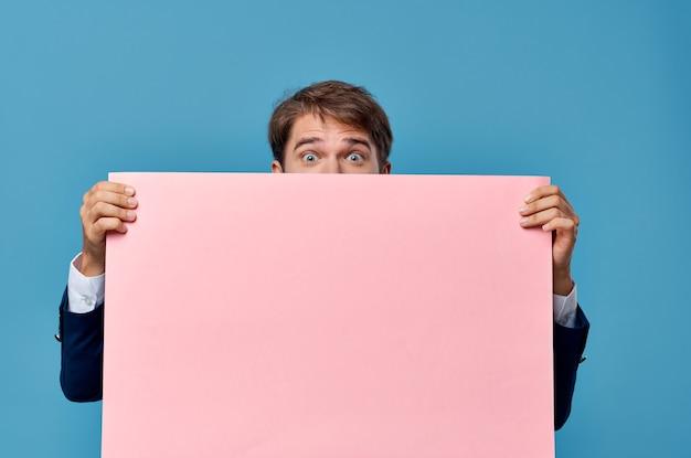 Emotionele man roze banner in de hand blanco blad presentatie geïsoleerde achtergrond