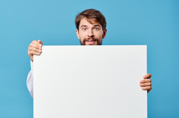 Emotionele man witte mockup poster in de hand reclame blauwe achtergrond