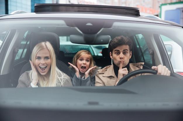 Emotionele man zit in de auto met zijn vrouw en dochter
