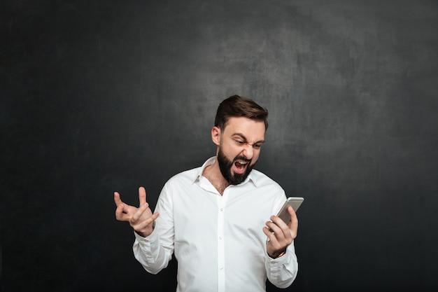 Emotionele mannelijke arbeider die in woede en verontwaardiging gilt terwijl het kijken op het scherm van zilveren smartphone over donkergrijs