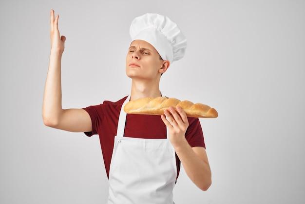 Emotionele mannelijke chef-kok in een wit schortbrood in de handen van kokend bakken