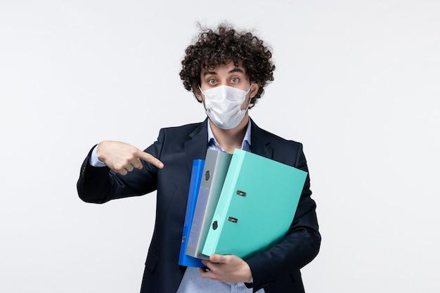 Emotionele mannelijke ondernemer in pak en het dragen van zijn masker met documenten die naar beneden wijzen op een wit oppervlak