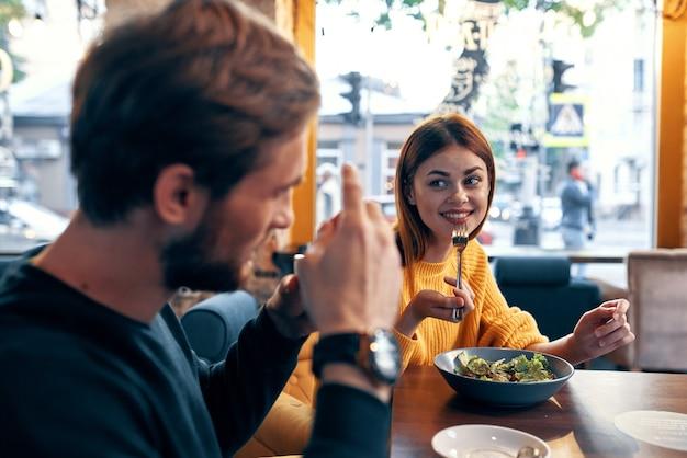 Emotionele mannen en vrouwen aan een tafel in een café, leuk getrouwd stel maaltijdsalade