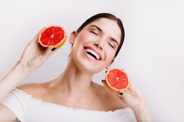 Emotionele meisje vol energie lacht en poseert met rode citrusvruchten in haar handen.