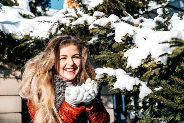 Emotionele meisje waait sneeuw in haar handen