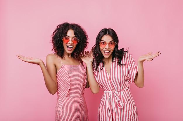 Emotionele meisjes laten een verbaasde gezichtsuitdrukking zien. dame in zomer roze zonnebril poseren voor portret.
