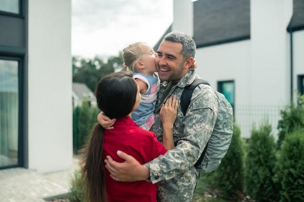 Emotionele militaire man. emotionele militaire man knuffelt zijn vrouw en dochter na thuiskomst