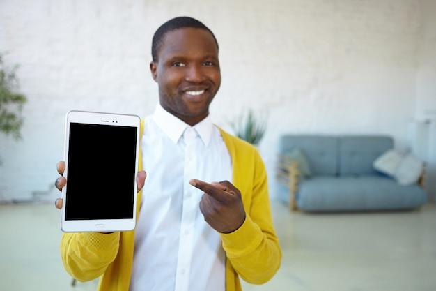 Emotionele modieuze donkere jongeman met brede glimlach modern elektronisch apparaat aan u tonen, digitale touchscreen tablet vasthouden, enthousiast over grote verkoopprijs, wijzende vinger op display