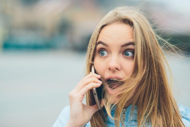 Emotionele mooie blonde praten aan de telefoon buitenshuis. vrouw corrupte gezichten en geeft zich over aan het chatten met vrienden op de cel.