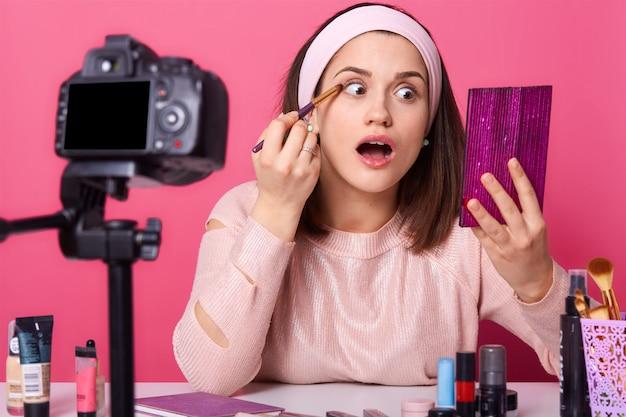 Emotionele mooie make-up artiest met wijd geopende mond met roze spiegel in één hand, oogschaduw aanbrengen met professionele borstel, video opnemen voor haar nieuwe vlog.