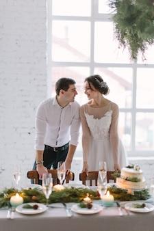 Emotionele mooie pasgetrouwde stel glimlachend, zoenen en knuffelen op bruiloft receptie in witte zaal met bruiloft decoraties
