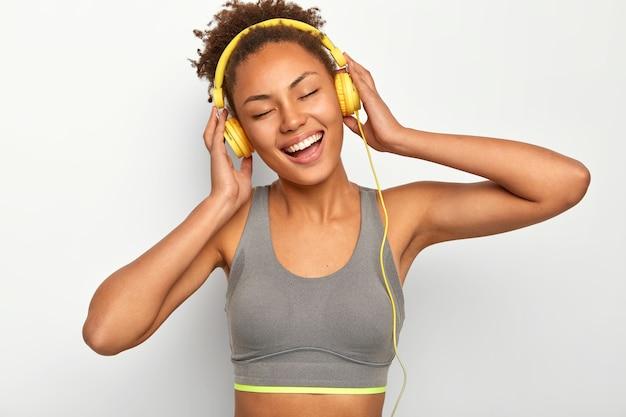 Emotionele mooie vrouw met krullend haar, lacht positief, geniet van luide muziek in hoofdtelefoons, houdt de ogen gesloten van plezier