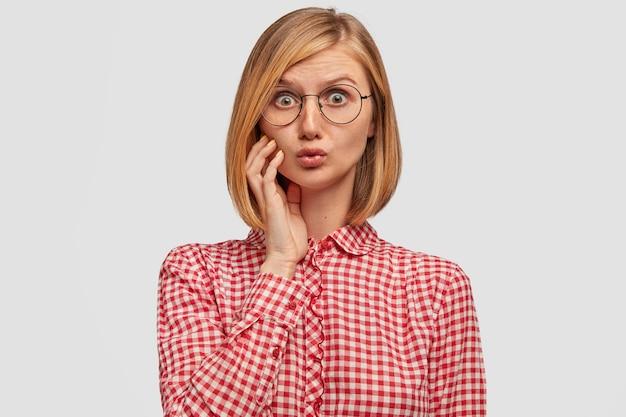 Emotionele mooie vrouw met verbaasde uitdrukking, kijkt verbaasd, ontvangt plotseling nieuws van gesprekspartner