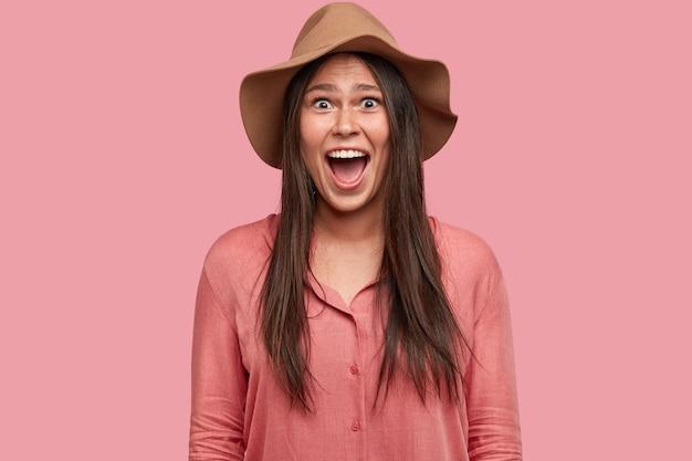 Emotionele mooie vrouwelijke tiener houdt de mond open, roept uit van geluk als ze opwindend nieuws ontdekt