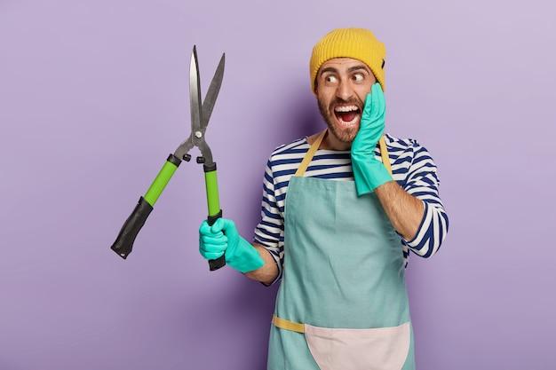 Emotionele onderhoudsmedewerker houdt snoeischaar, gekleed in werkkleding, snijdt takken, geïsoleerd op violette achtergrond.