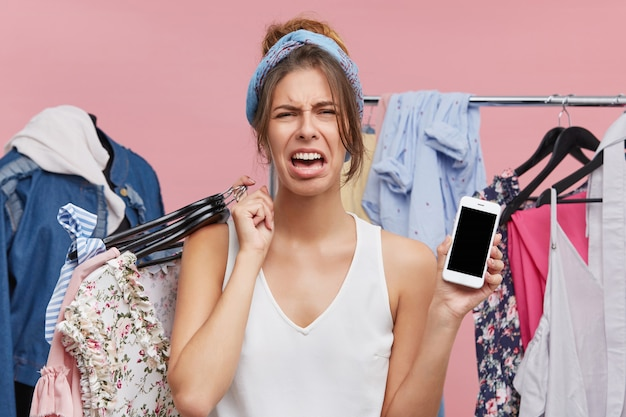 Emotionele ongelukkige vrouw die gefrustreerd voelt, huilend omdat ze geen geld heeft op bankaccountant om modieuze dure kleding te kopen die in de kleedkamer staat, mobiel met een kopieerscherm