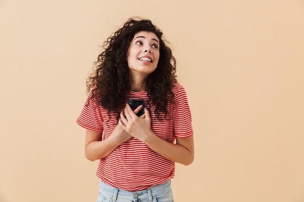 Emotionele opgewonden gelukkige jonge vrouw met behulp van mobiele telefoon.