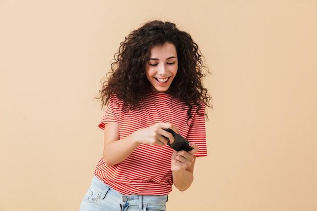 Emotionele opgewonden jonge krullende vrouw spelletjes spelen via de mobiele telefoon.