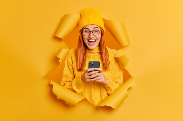 Emotionele opgewonden roodharige vrouwelijke student gebruikt moderne mobiele telefoon voor het verzenden van sms-chats online met groepsgenoten hoort uitstekend nieuws draagt gele kleding. Gratis Foto