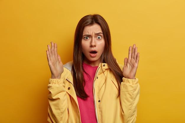 Emotionele opgewonden vrouw kijkt met verbaasde ontevreden uitdrukking, trekt wenkbrauwen op, opent mond, heft handpalmen op en vormt iets groots