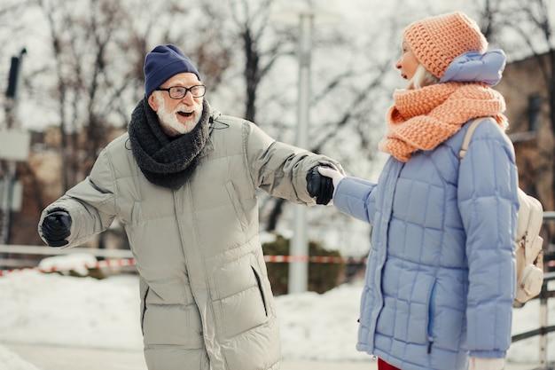 Emotionele oudere man die op de ijsbaan staat met zijn geliefde vrouw en glimlacht terwijl hij op het ijs balanceert en haar hand vasthoudt