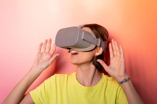 Emotionele portret van vrouw in virtual reality-bril in studio op roze oranje achtergrond