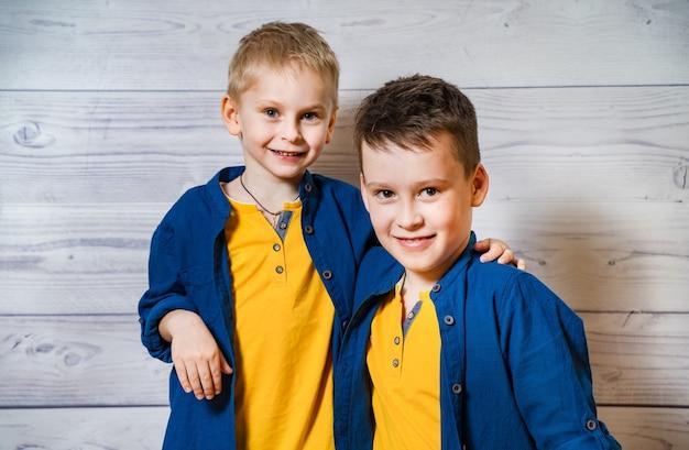 Emotionele portretten van gelukkige en positieve broertjes, die naar de camera kijken en glimlachen, elkaar knuffelen
