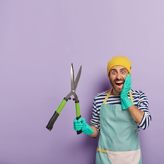 Emotionele positieve mannelijke tuinman houdt scherpe snoeischaar, klaar voor het knippen van struiken of bomen, draagt rubberen handschoenen, blauwe aproon