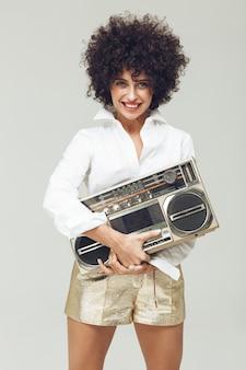 Emotionele retro vrouw gekleed in overhemd die boombox houden.
