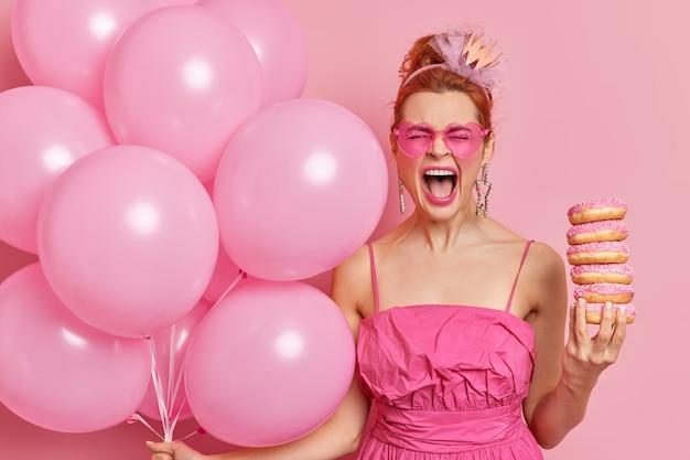 Emotionele roodharige jonge vrouw roept luid en houdt mond wijd open komt op verjaardagsfeestje