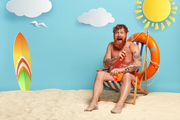 Emotionele roodharige poseren op het strand met zonnebrandcrème