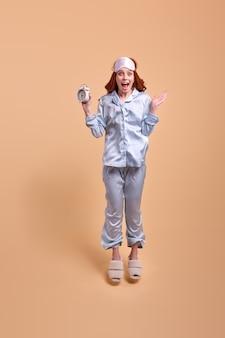 Emotionele roodharige vrouw geïsoleerd op beige achtergrond in pyjama, klok met verbaasde gezichtsuitdrukking, springen. oogmasker op voorhoofd, vrouwelijke blik op camera, portret. kopieer ruimte