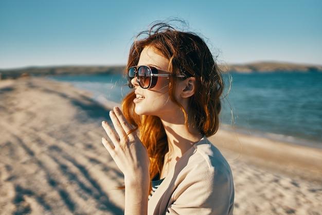 Emotionele roodharige vrouw in een jas houdt handen in de buurt van het gezicht in de natuur in de buurt van de zee
