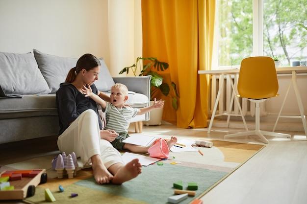 Emotionele schattige blanke jongen zittend met papier op knieën en uitgestrekte armen terwijl hij thuis een verhaal vertelt aan moeder