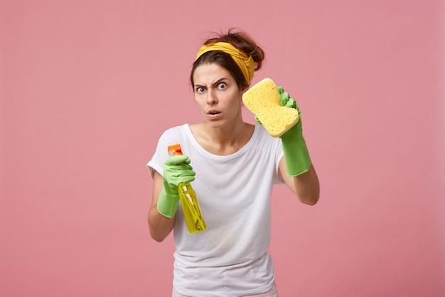 Emotionele schattige vrouw poseren in groene rubberen handschoenen, uitgerust met gele spons en spray wasmiddel, klaar voor het opruimen en schoonmaken van huis, kijkend met grappige uitdrukking op haar gezicht