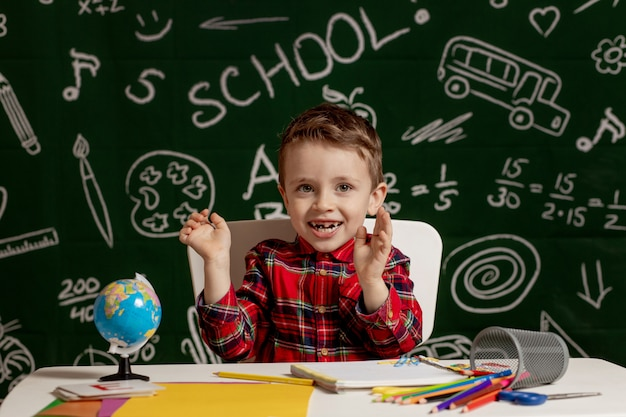 Emotionele schooljongen zittend op het bureau met veel schoolbenodigdheden. eerste schooldag. kid jongen van de basisschool. terug naar school. kind van de basisschool.
