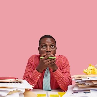 Emotionele sprakeloze donkere ondernemer merkt iets vreselijks naar boven, gekleed in een elegant overhemd met stropdas, omringd met stapels papieren en boeken