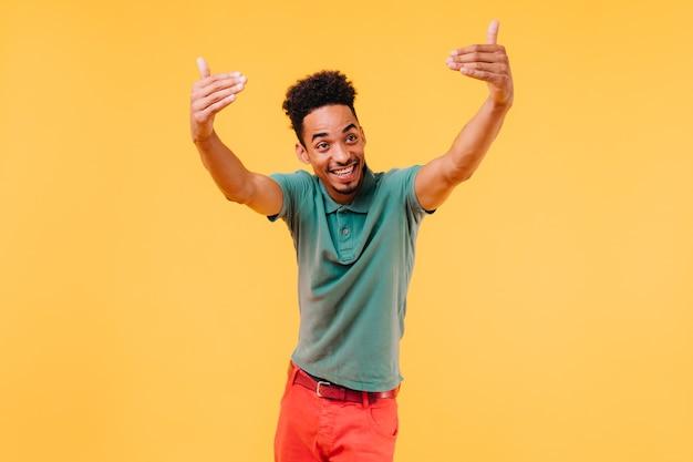Emotionele stijlvolle man in groen t-shirt met plezier. zorgeloze zwarte man zwaaiende handen.