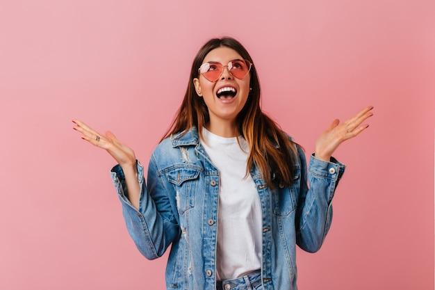 Emotionele stijlvolle vrouw opzoeken op roze achtergrond. verrast brunette meisje in denim jasje poseren met open mond.