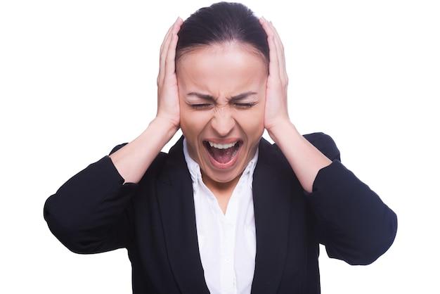 Emotionele stress. gefrustreerde jonge vrouw in formele kleding die oren bedekt met handen en ogen gesloten houdt terwijl ze geïsoleerd op wit staat